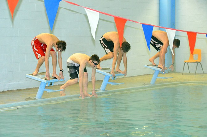 Image of novice high school boy swimmers doing a swim start from the blocks