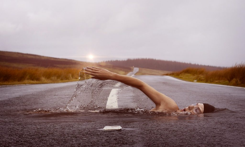 Image of swimmer crossing a road swimming freestyle